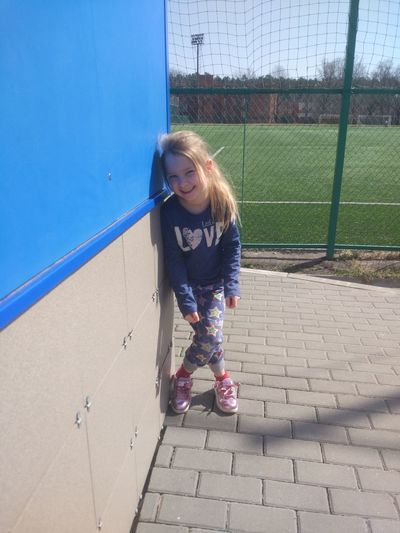 Portrait of girl standing by building