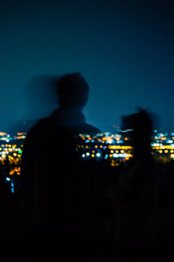 Rear view of silhouette man standing against illuminated city at night