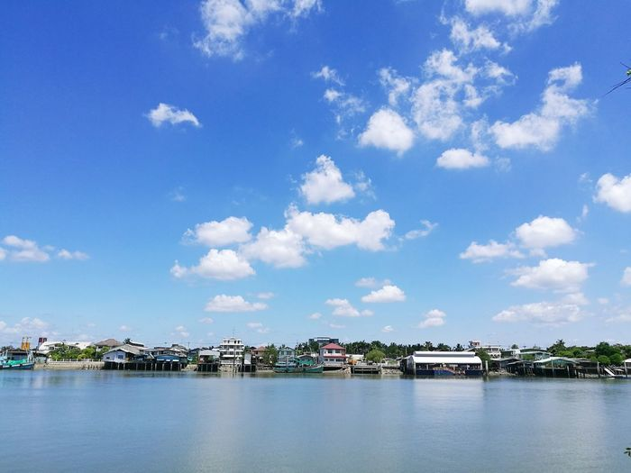 Lake by houses against blue sky