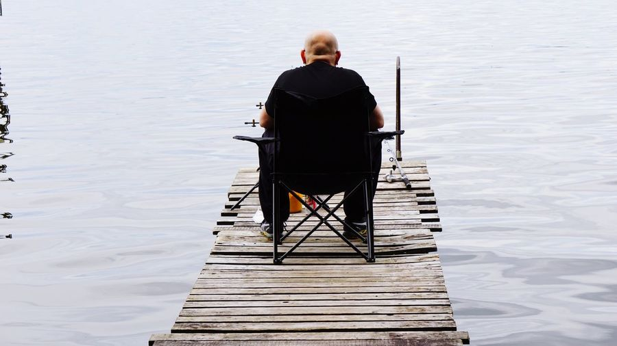 Rear View Of Bald Man Sitting On Pier Over Lake