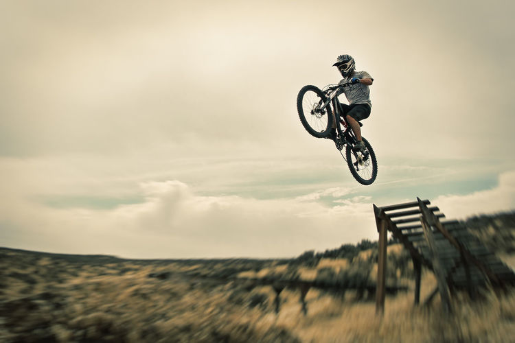 Man Performing Stunt On Bicycle Against Sky
