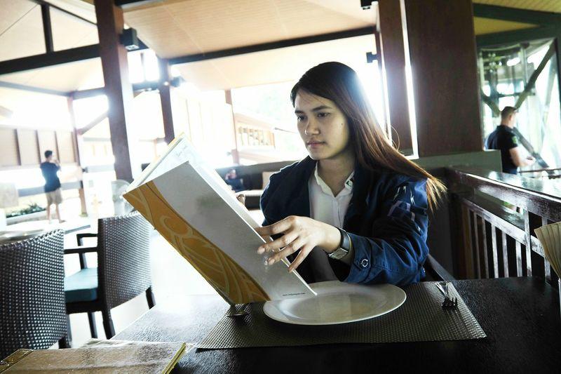 Woman reading menu while sitting at restaurant