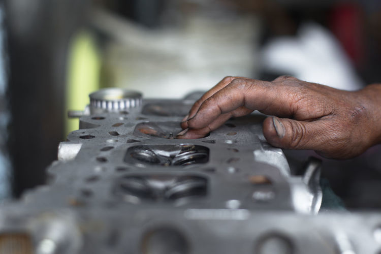 Close-up of mechanic hand on engine at repair shop