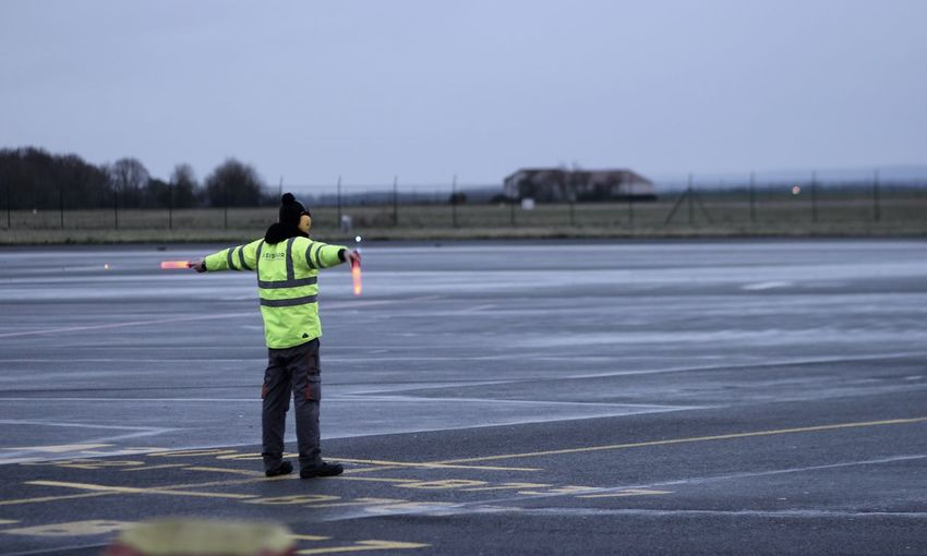 Rear view of man standing on runway