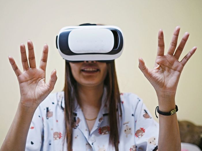 Woman gesturing while using virtual reality simulator