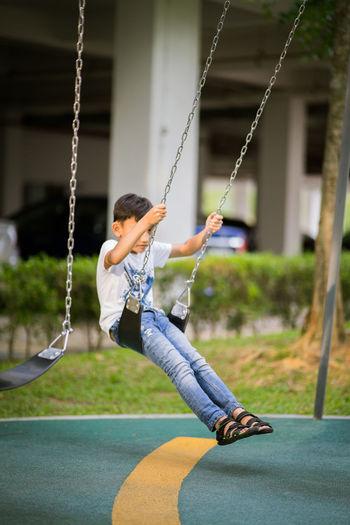 Boy playing on swing at playground