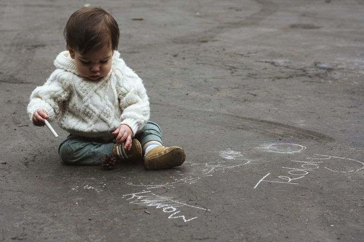 Baby boy sitting on asphalt with crayon