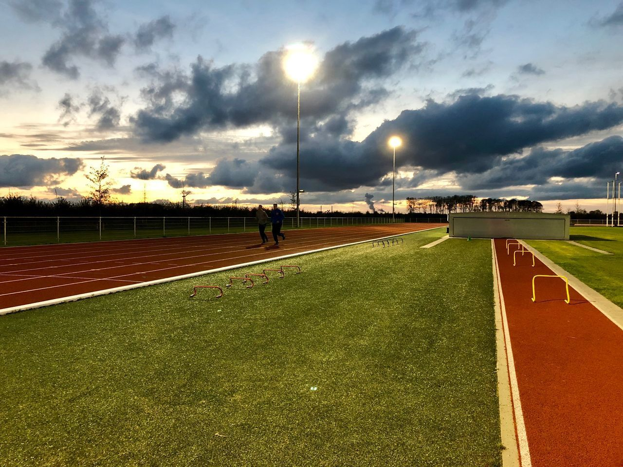 cloud - sky, sky, sport, nature, grass, track and field, running track, sports track, sunset, built structure, real people, incidental people, architecture, sunlight, outdoors, plant, people, men, building exterior, day
