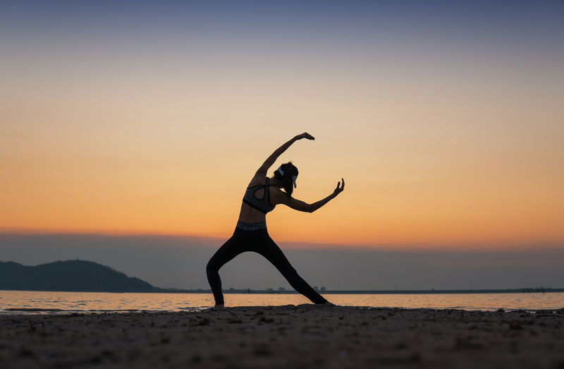 Full length of woman exercising at beach during sunset