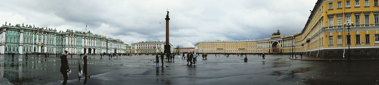 Panoramic View Of People At Palace Square Against Cloudy Sky