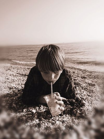 Childhood Childhood Beach Drink Softdrink Straw Perspective Filter Focus On Foreground Portrait Boy Pebbles Beachlife Edit Chilling Close-up Sepia Child Water Sea Beach Sand Summer Sunlight Clear Sky Wave Sky Horizon Over Water