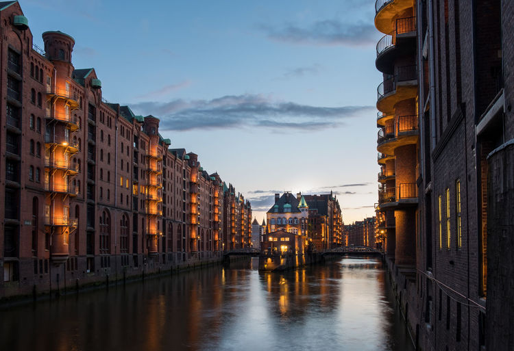 Canal amidst buildings at speicherstadt in city during dusk