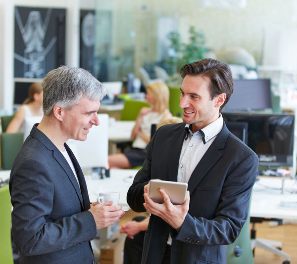 Businessman holding digital tablet while discussing with colleague in office