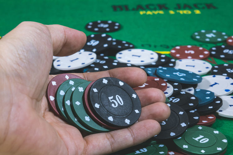 Cropped hand holding gambling chips