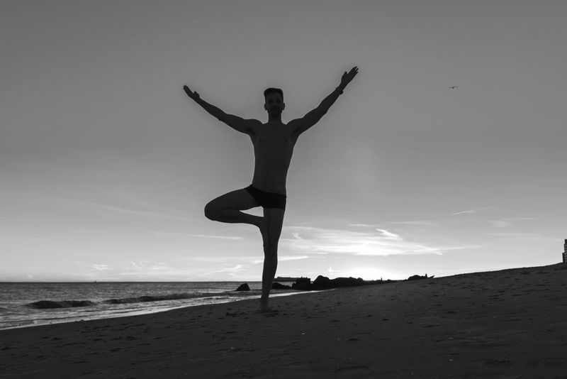 Silhouetted man doing a yoga pose tree stand with arms raised up at sunset on the beach in black and white. Yoga Yoga Pose Arms Raised Balance Beach Beauty In Nature Black And White Exercising Flexibility Full Length Healthy Lifestyle Leisure Activity Lifestyles Nature One Person Outdoors Practicing Real People Sand Sea Sky Tree Pose Water Young Adult Zen