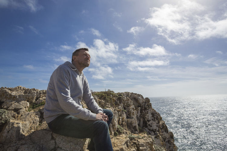 Adult man sitting on the rock and looking up. 45-50 Algarve Happy Jeans Man Portugal Relaxing Rock Sitting Sunlight Thinking Tranquility A Casual Clothing Hood - Clothing Horizon Looking Ocean One Man Only Outdoors Peaceful Sea Seascape Sky Space