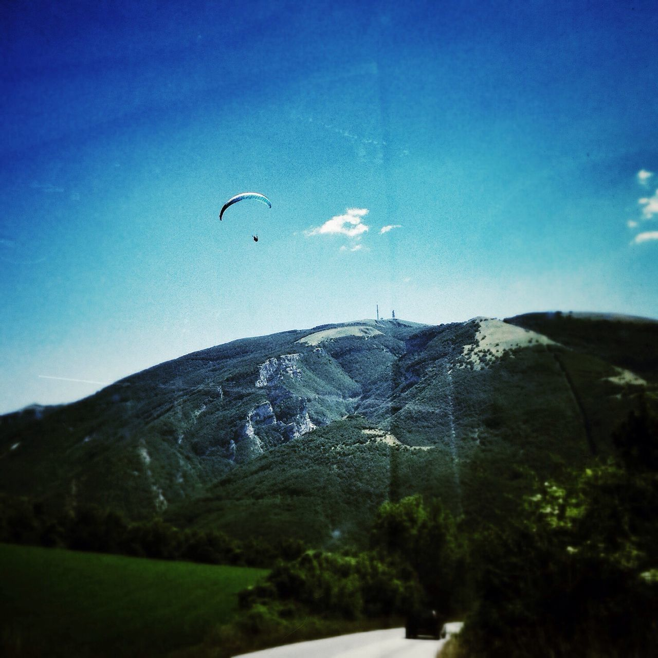 mountain, nature, tranquility, sky, outdoors, tranquil scene, day, beauty in nature, blue, scenics, landscape, no people, adventure, flying, tree, paragliding