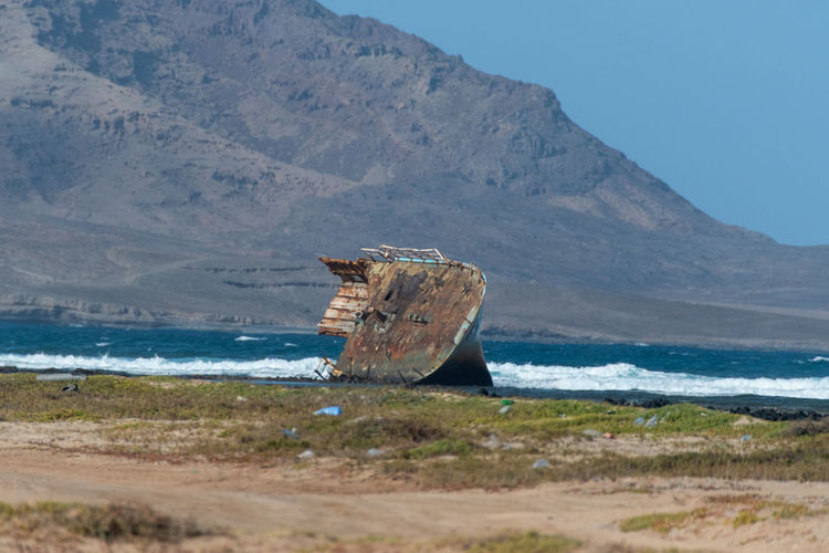 Hoffi99 Sea Water Mountain Land Shipwreck Beach Nature Beauty In Nature Day Ship Tranquility Nautical Vessel Scenics - Nature Sky Tranquil Scene No People Transportation Mode Of Transportation Sand Outdoors Deterioration