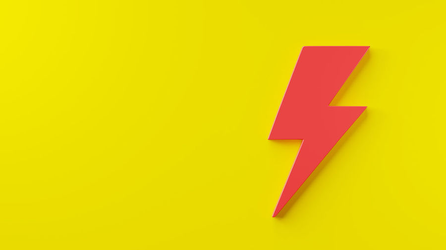 Close-up of arrow sign on yellow background