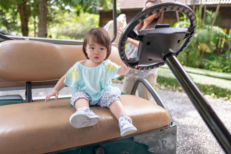 Portrait Of Cute Girl Sitting By Mother Standing On Golf Cart
