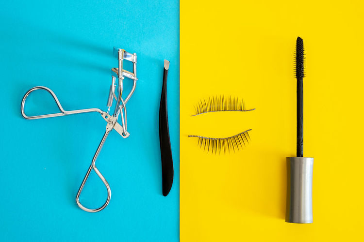 High angle view of eye make-up equipment on colored background