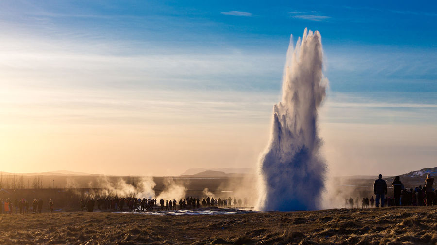 People standing by geyser on field against sky