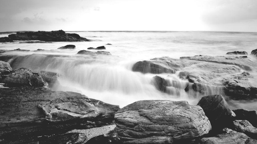 Waves rushing over rocks against sky