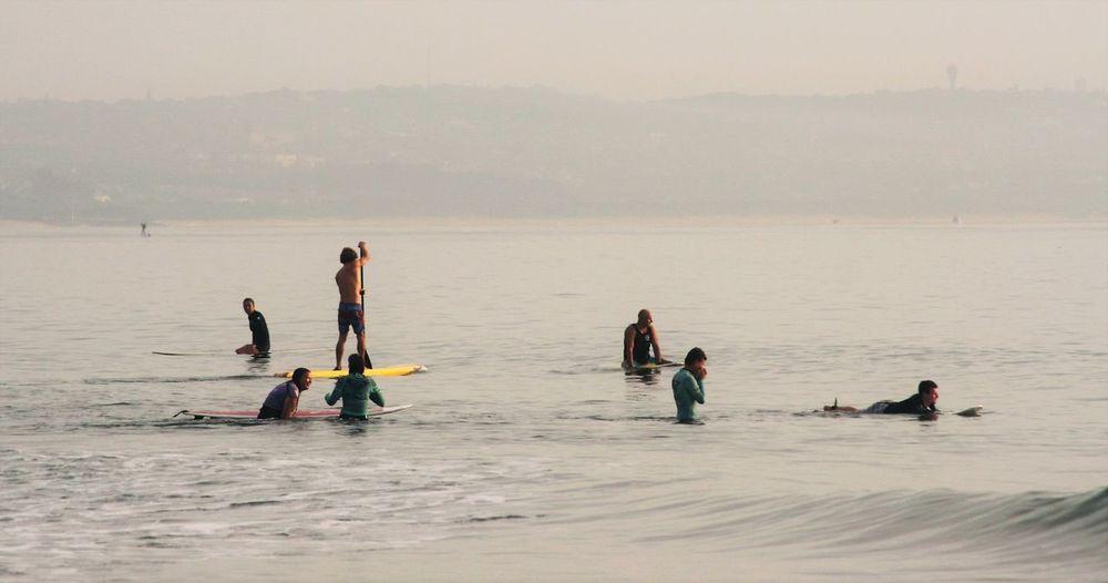 People enjoying in sea during foggy weather