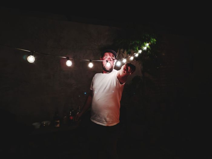 Man standing by illuminated decoration