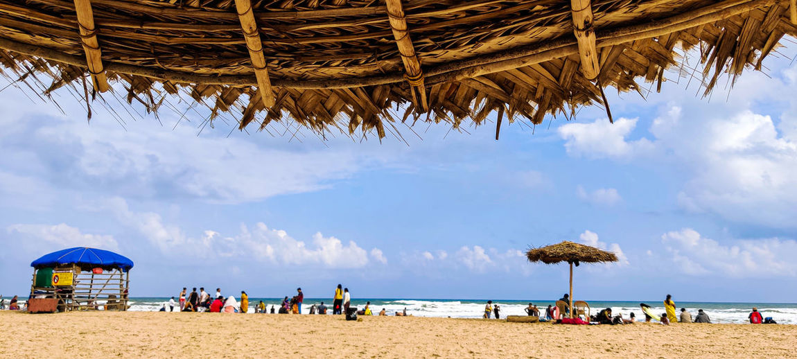 Group of people on beach against sky