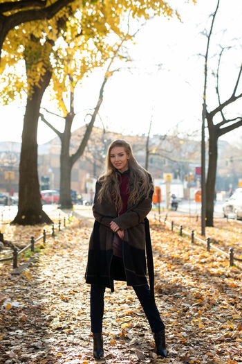Portrait of young woman standing against trees during autumn
