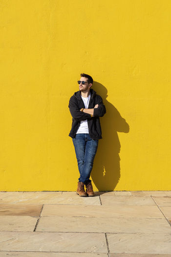 Full length of young man standing against yellow wall