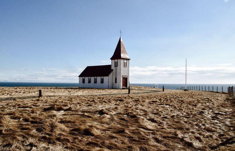 Beach by building against sky