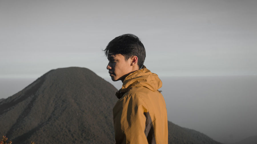 Side view of young man looking at mountains against sky