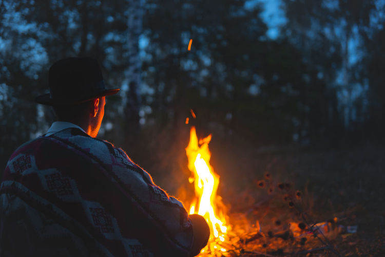 Rear view of man with bonfire in forest