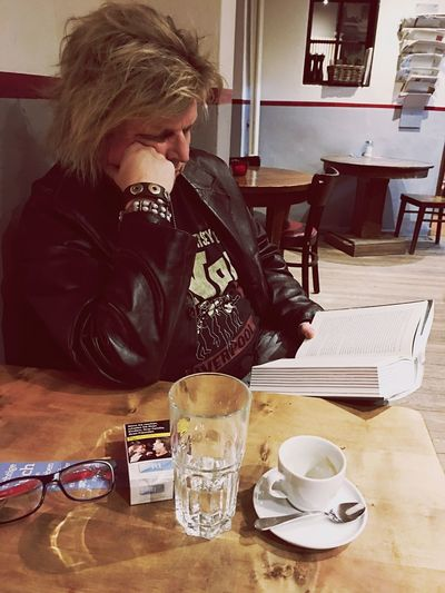 Rocker reading a book Sitting Coffee - Drink Coffee Cup Table Drink Refreshment Food And Drink Indoors  Saucer One Person Leisure Activity Lifestyles Real People Full Length Books Home Interior Only Women Warm Clothing Adults Only People Rock Rock - Object Rock Formation Rock N Roll Book
