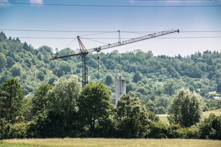 Big crane in the middle of the german countryside Architecture Built Structure Cable Connection Construction Industry Crane - Construction Machinery Day Green Color Growth Land Landscape Low Angle View Machinery Nature No People Outdoors Plant Power Supply Sky Sunlight Tree