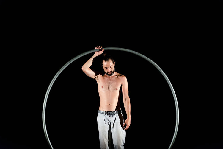 Circus Adult Black Background Front View Human Arm Indoors  Lifestyles Men Muscular Build One Person Plastic Hoop Real People Shirtless Skill  Standing Strength Studio Shot Three Quarter Length Young Adult Young Men