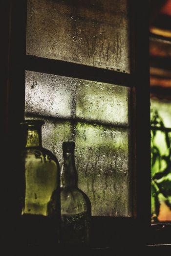 Close-up of glass of bottles on window