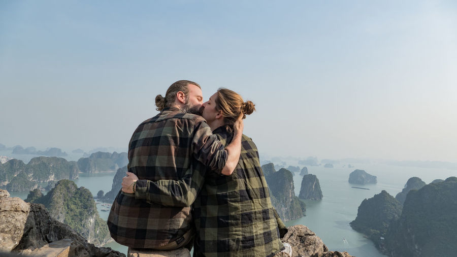 Couple kissing on mountain against clear sky