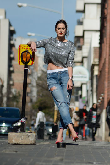 Full length of fashionable woman standing on street in city