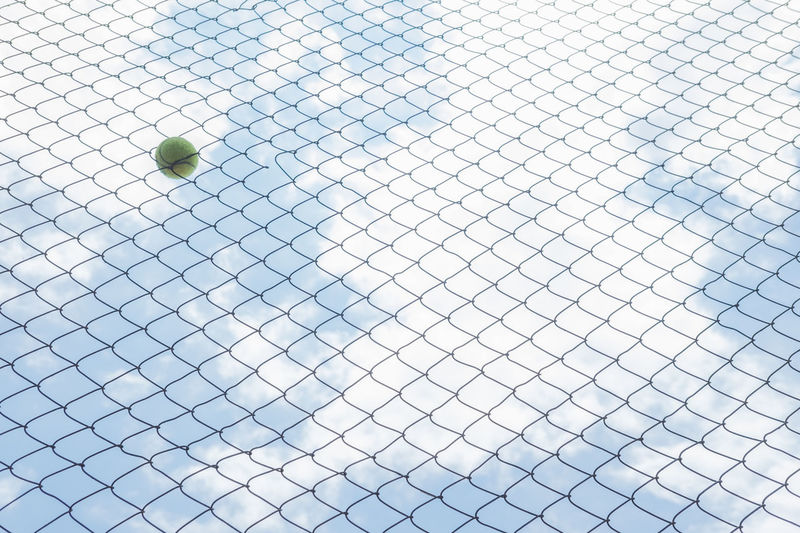 Low Angle View Of Ball On Fence Against Sky