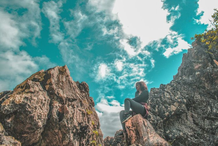 Low angle view of person sitting on rock against sky
