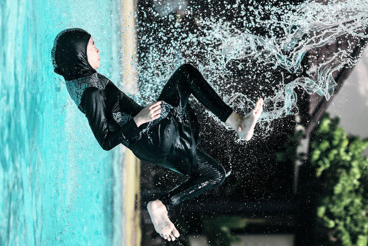 Teenage girl diving in swimming pool