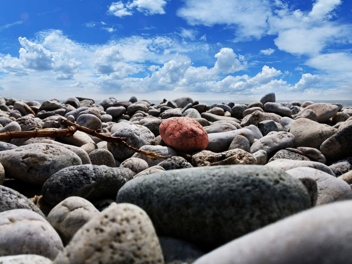 Surface level of pebbles at beach against sky