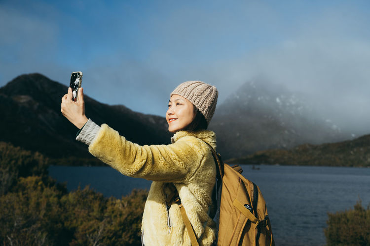 Young man photographing on mobile phone in winter
