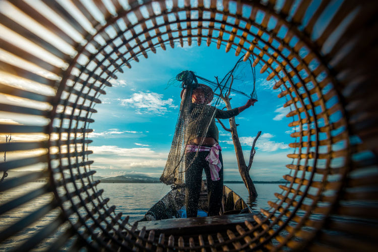 Fishermen are fishing Day Sky Architecture Real People One Person Nature Basket Full Length Built Structure Outdoors Blue Standing Adult Container Young Adult Travel Fisherman Water