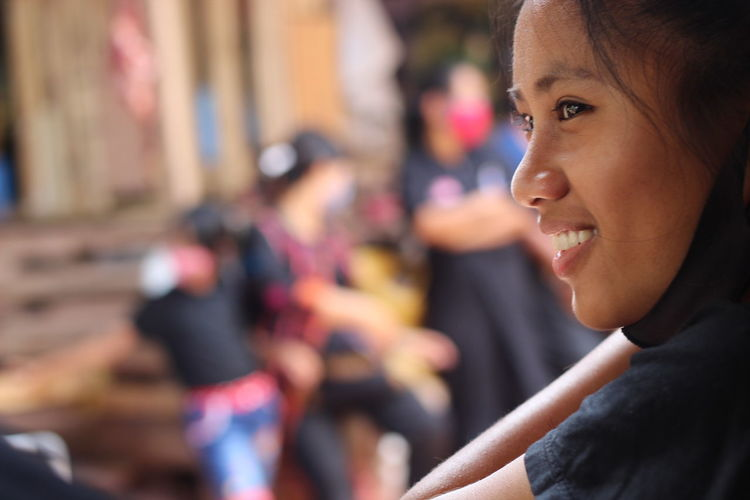 Close-up portrait of smiling young woman looking away outdoors