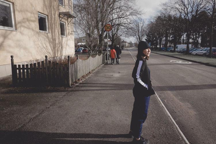 Side view of man walking on street in city