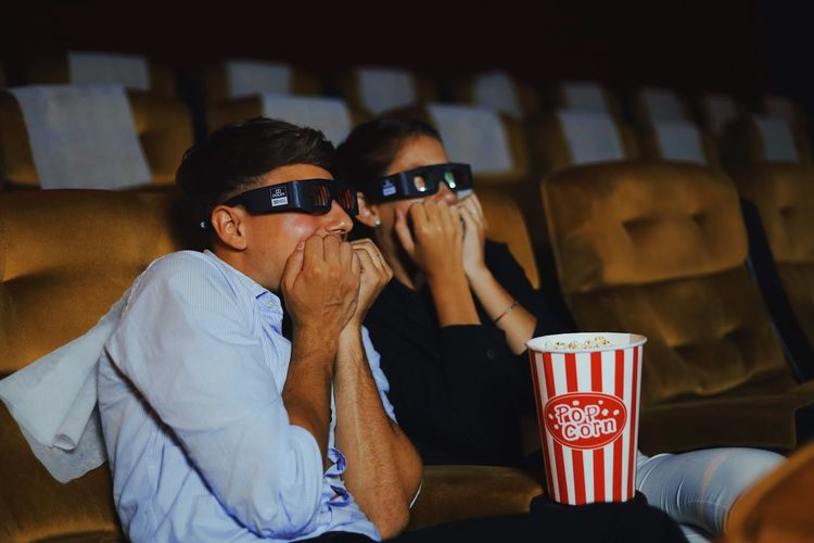 Scared couple watching movie in theater